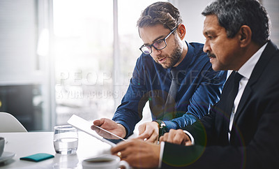 Buy stock photo Cropped shot of two businesspeople working on a digital tablet
