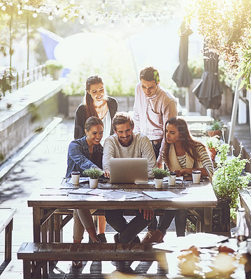 Buy stock photo Shot of a team of colleagues using a laptop together during a meeting at an outdoor cafe