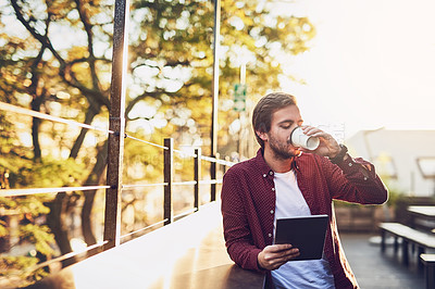 Buy stock photo Cropped shot of a handsome man using his digital tablet while drinking coffee outside
