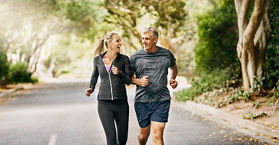 Buy stock photo Shot of a mature couple out jogging on a sunny day