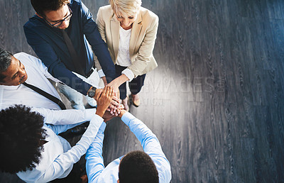 Buy stock photo Shot of a group of businesspeople joining their hands together in unity in an office