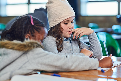 Buy stock photo Cropped shot of elementary school girls doing school work together in the classroom