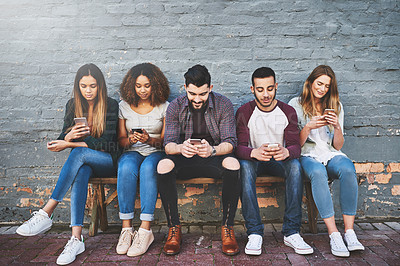 Buy stock photo Shot of a group of young friends using their mobile phones outdoors