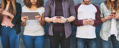 Buy stock photo Shot of a group of young friends using their wireless devices together outdoors