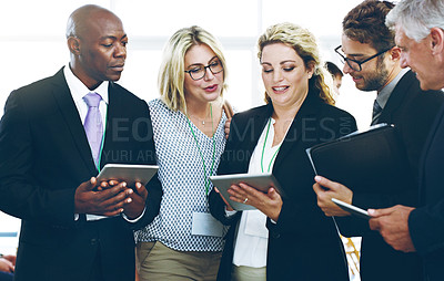 Buy stock photo Cropped shot of a group of corporate businesspeople standing in a huddle with digital tablets in hand