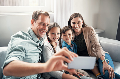 Buy stock photo Shot of a happy family taking a selfie together on a mobile phone at home