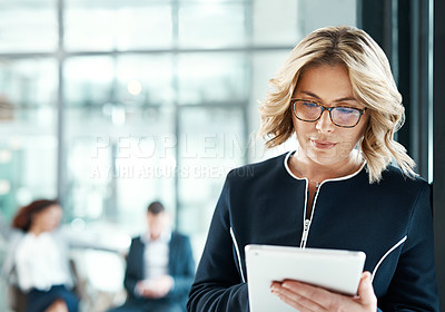 Buy stock photo Shot of a businesswoman using a digital tablet in a modern office with her colleagues in the background