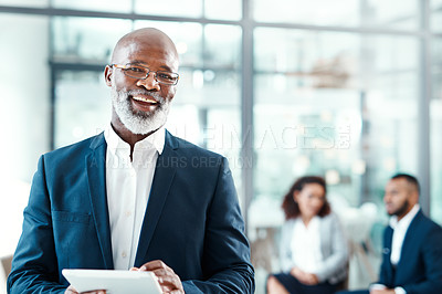 Buy stock photo Portrait of a mature businessman using a digital tablet in a modern office with his colleagues in the background