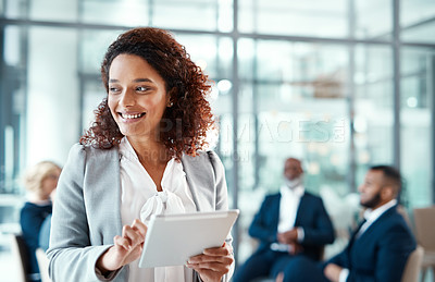 Buy stock photo Shot of a young businesswoman using a digital tablet in a modern office with her colleagues in the background