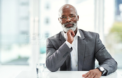 Buy stock photo Portrait of a confident mature businessman sitting at his desk in a modern office