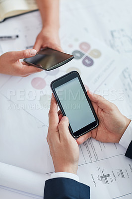 Buy stock photo Cropped shot of two businesspeople using their cellphones at a desk