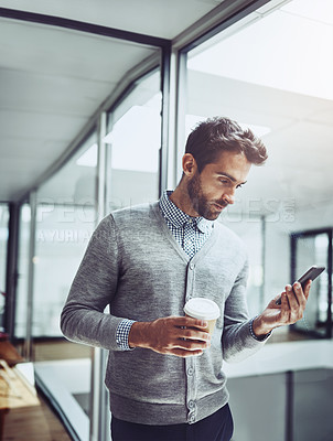 Buy stock photo Cropped shot of a handsome young businessman looking at his cellphone while standing in the office