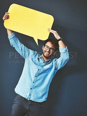 Buy stock photo Studio portrait of a young man holding a speech bubble against a grey background