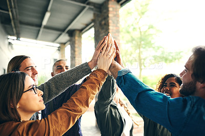 Buy stock photo Shot of a group of young students joining their hands together in solidarity on campus