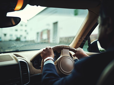 Buy stock photo Rearview shot of a businessman driving a stylish car