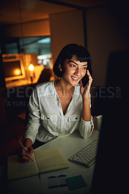 Buy stock photo Shot of a young businesswoman using a mobile phone and computer during a late night at work