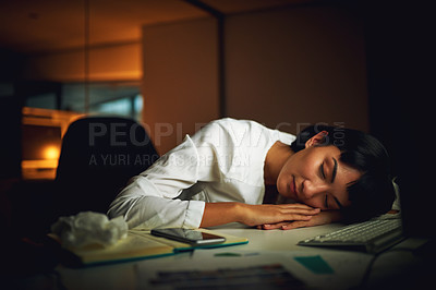 Buy stock photo Shot of a young businesswoman sleeping at her desk during a late night at work