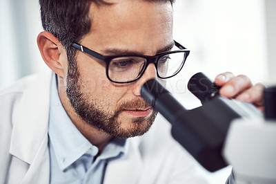 Buy stock photo Shot of a focused young male scientist looking through a microscope while being seated inside of a laboratory