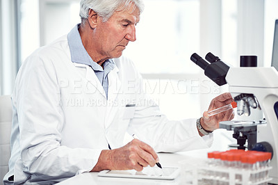 Buy stock photo Shot of a focused elderly male scientist holding up a test tube and making notes while being seated inside of a laboratory