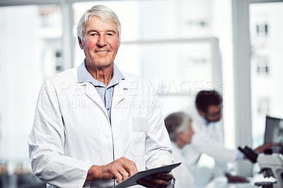Buy stock photo Portrait of cheerful elderly male scientist using a digital tablet while looking into the camera inside a laboratory