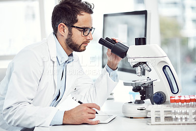 Buy stock photo Shot of a focused young male scientist making notes and looking through a microscope while being seated inside of a laboratory