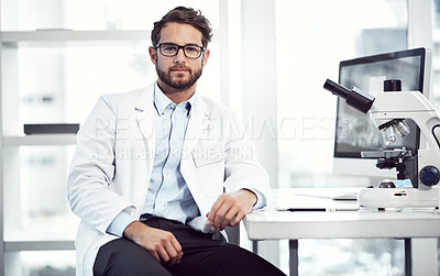 Buy stock photo Shot of a confident young male scientist looking into the camera while being seated inside of a laboratory