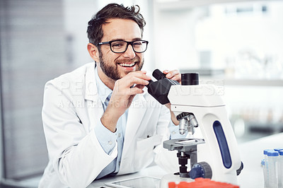 Buy stock photo Shot of a cheerful young male scientist looking through a microscope while being seated inside of a laboratory