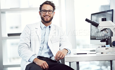 Buy stock photo Shot of a cheerful young male scientist looking into the camera while being seated inside of a laboratory