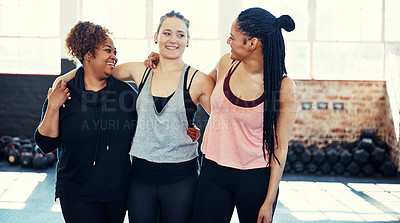 Buy stock photo Shot of three cheerful young women having a conversation while holding each other before a workout session in a gym