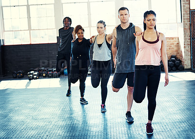 Buy stock photo Shot of a focused group of young people standing in a row and stretching before a workout session in a gym