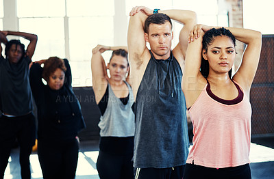 Buy stock photo Shot of a focused group of young people standing in a row and stretching while one looks into the camera in a gym
