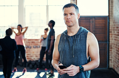 Buy stock photo Shot of a focused young man standing and using his cellphone while contemplating before a workout in a gym