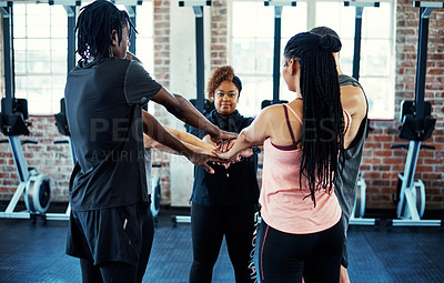 Buy stock photo Shot of a focused young group of people forming a huddle together while one looks into the camera before a workout in a gym