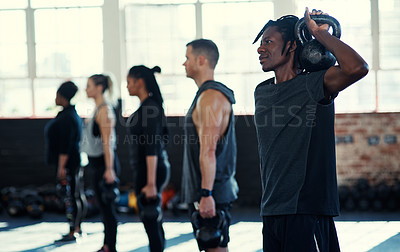 Buy stock photo Shot of a focused group of young people standing in a row and training with weights in a gym