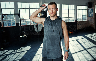 Buy stock photo Shot of a young man lifting kettlebells in a gym