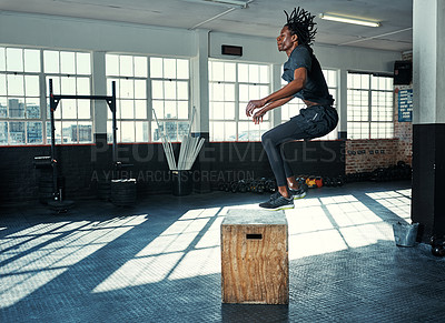 Buy stock photo Shot of a young man doing jumping exercises on a wooden block in a gym