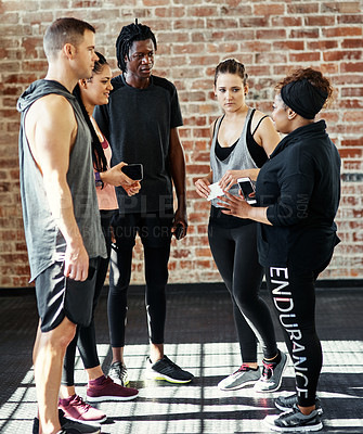 Buy stock photo Shot of a cheerful young group of people standing in a circle and having a conversation before a workout in a gym
