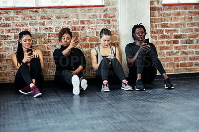 Buy stock photo Shot of a cheerful young group of people sitting down the floor and using their cellphones before a workout in a gym