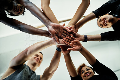 Buy stock photo Low angle shot of a cheerful young group of people forming a huddle together before a workout session in a gym