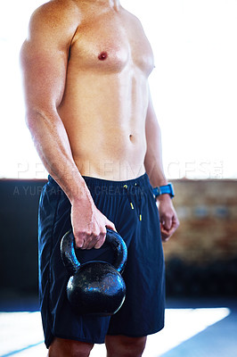 Buy stock photo Shot of an unrecognizable man lifting kettlebells in a gym
