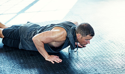 Buy stock photo Shot of a young man doing push ups in a gym