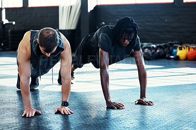 Buy stock photo Shot of young men doing push ups in a gym