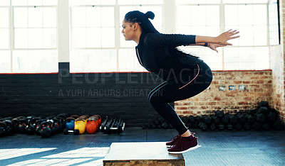 Buy stock photo Shot of a young woman doing a exercise jump on a wooden block in a gym