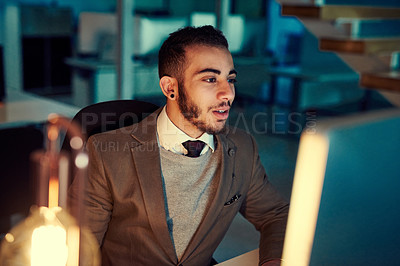 Buy stock photo Shot of a young businessman working late in an office