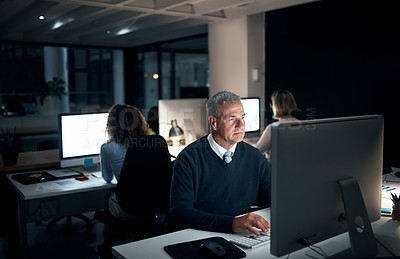 Buy stock photo High angle shot of a handsome mature businessman working late at the office
