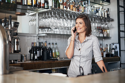 Buy stock photo Cropped shot of an attractive young woman using a cellphone while standing in her coffee shop