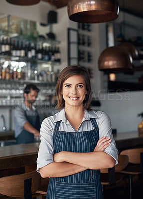 Buy stock photo Cropped portrait of an attractive young woman standing with her arms folded in her coffee shop
