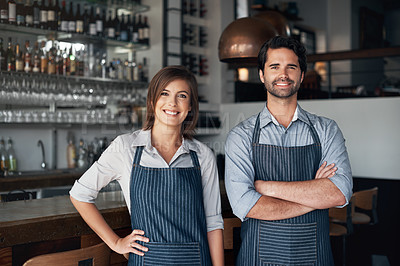 Buy stock photo Cropped portrait of two young entrepreneurs standing side by side in their coffee shop