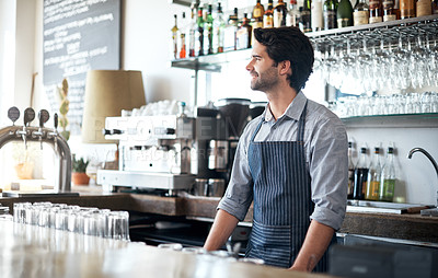 Buy stock photo Cropped shot of a handsome young man working behind the bar in his coffee shop