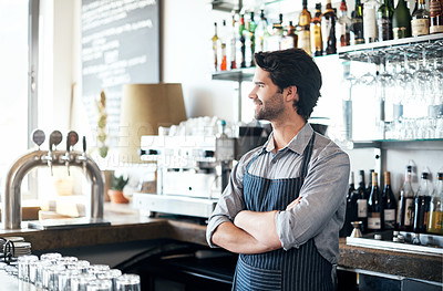 Buy stock photo Cropped shot of a handsome young man standing with his arms crossed behind he bar in his coffee shop